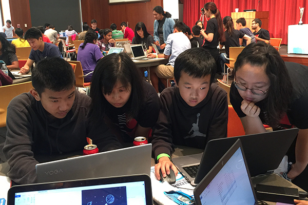 Students sit around a table and work on laptops at hackathon