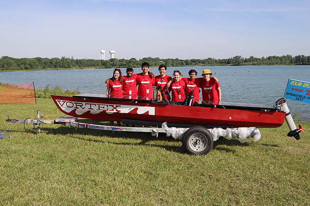 Team members pose behind boat