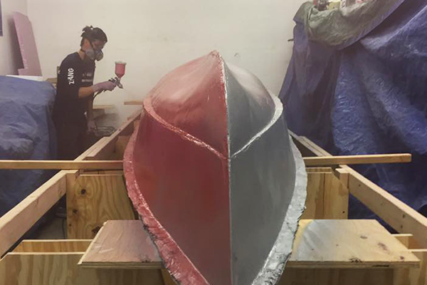 Students prepare the mold for the boat