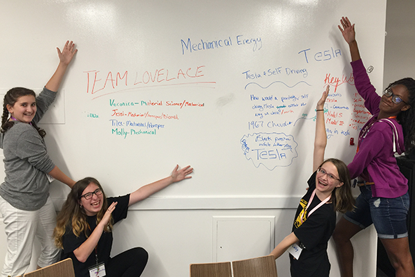 4 female students pointing at whiteboard