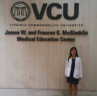 Huang in white coat in front of VCU sign