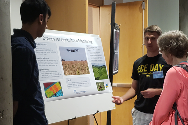 Student talking beside research poster