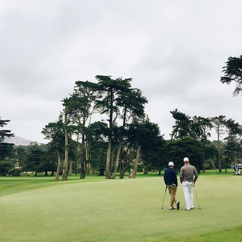 2 people standing on golf course
