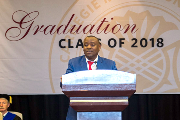 Hon. Isaac Munyakazi speaking at podium at graduation