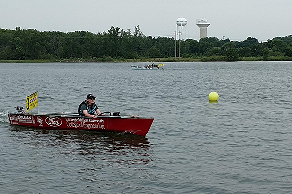Student in boat in water, racing