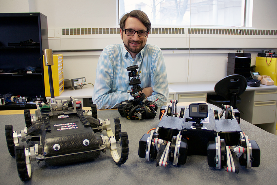Aaron Johnson in his lab with some of his robots.