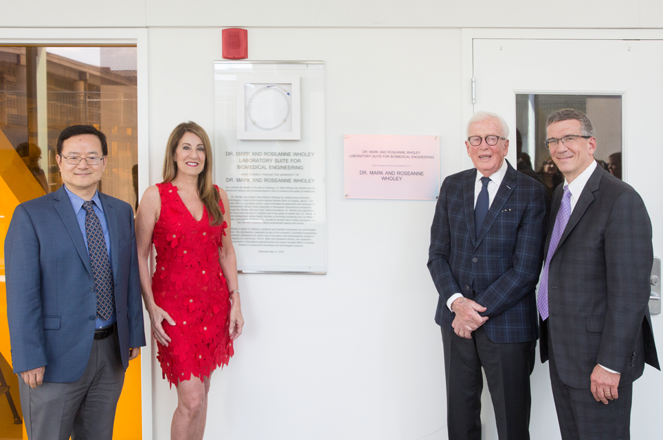 The Wholeys posing on either side of the entrance to the new lab, with the provost and BME department head.