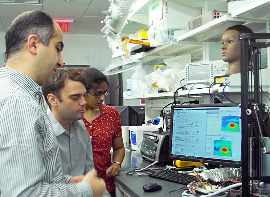 Maysam Chamanzer and two students in the lab looking at a computer screen