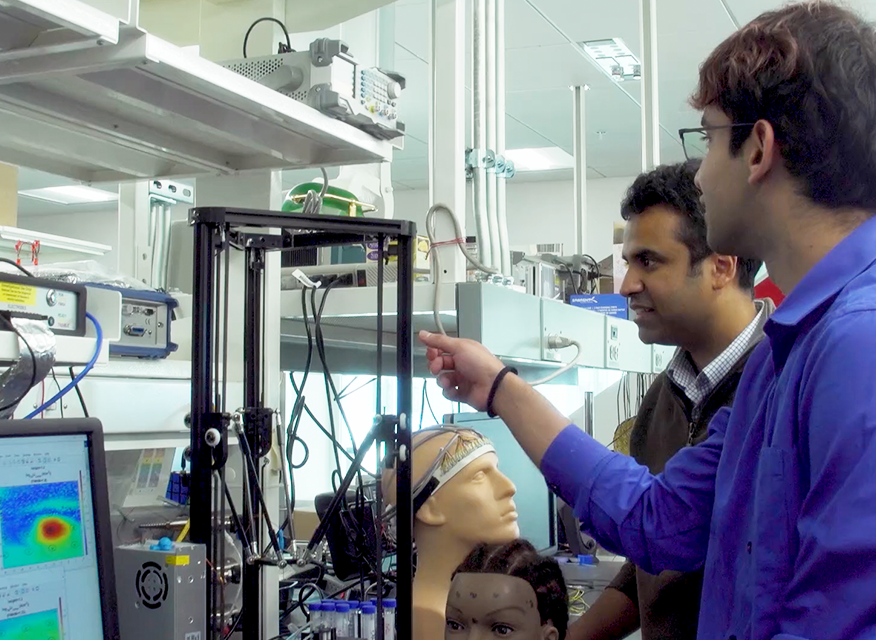 Pulkit Grover and a student in the lab with their wearable sensor.