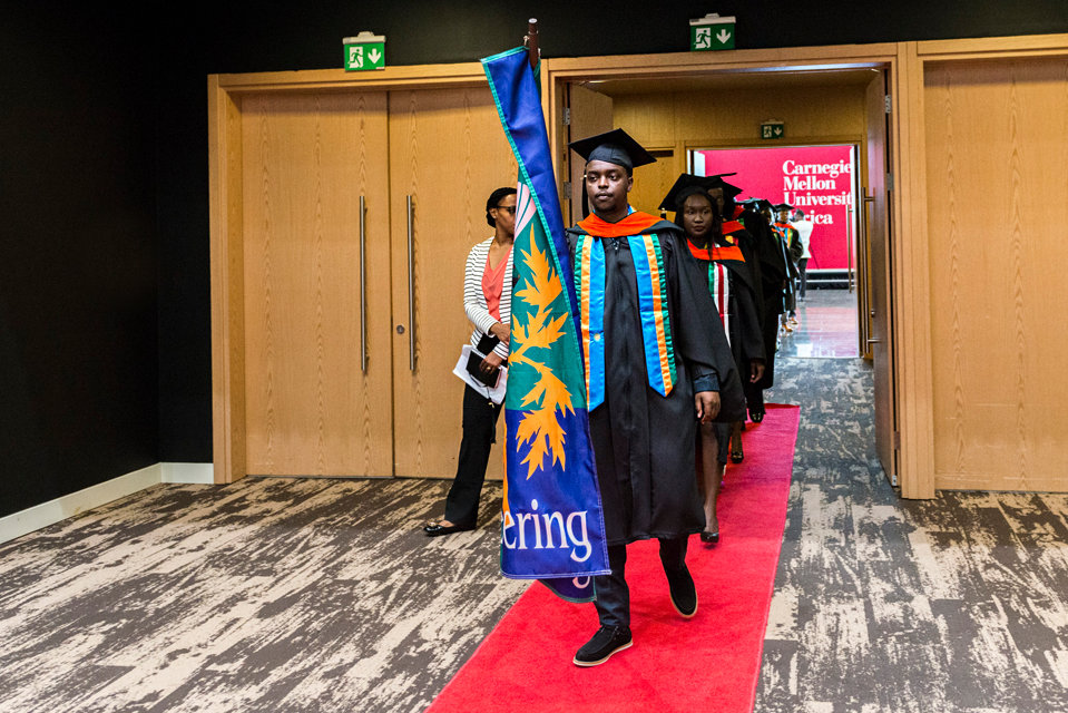 Photo of a CMU Africa student carrying the CMU Engineering flag