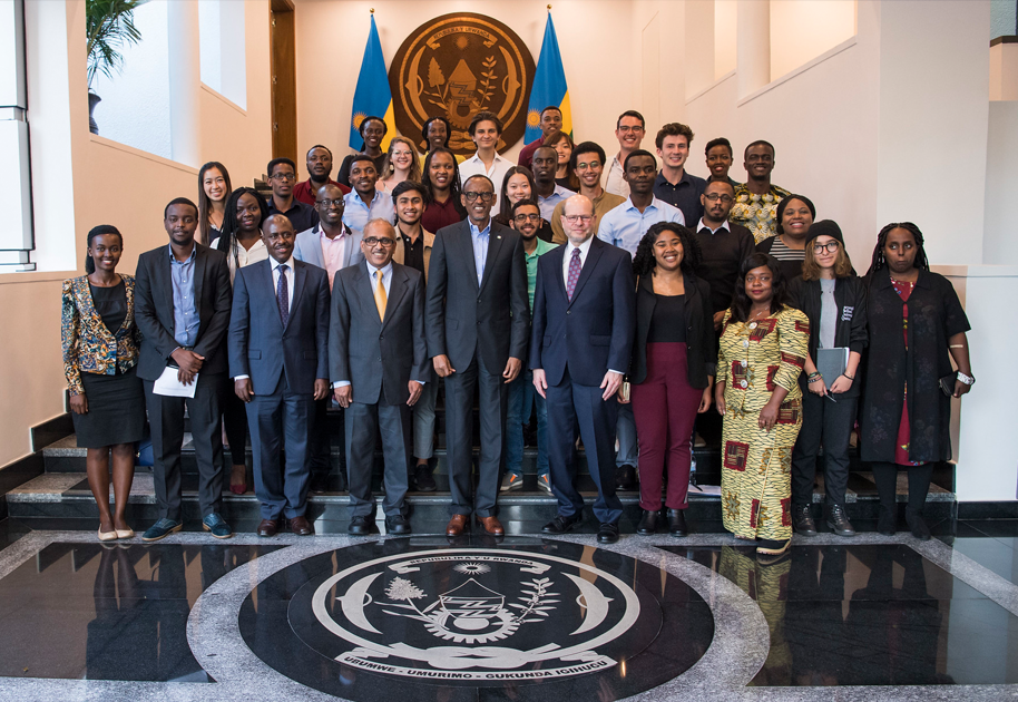 President Kagame posing with students for a group shot.