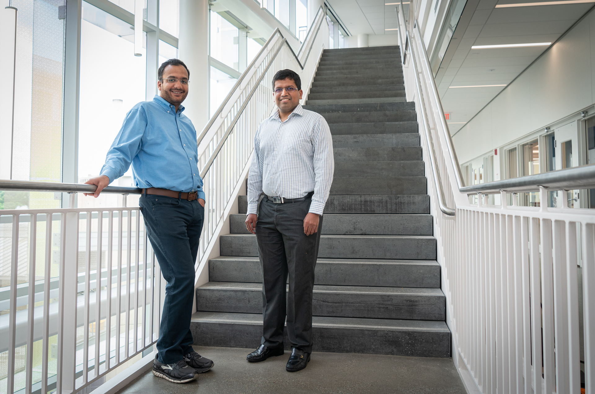 Two men, Rahul Panat and Vipul Goyal, standing in the stairway of Scott Hall on CMU's campus.