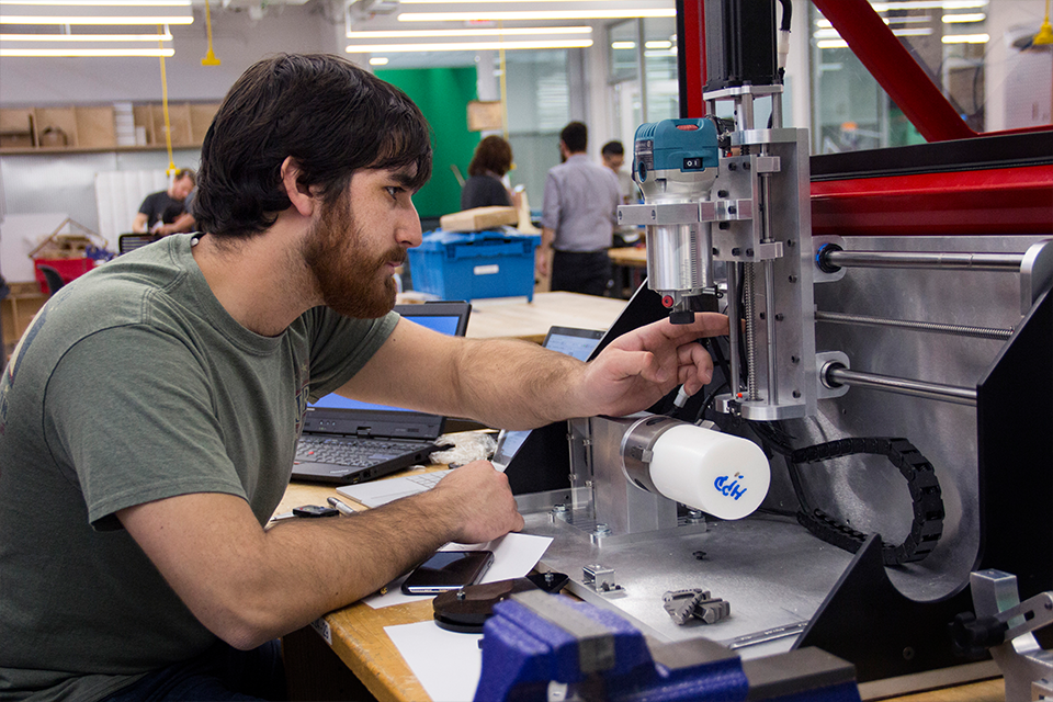 Student in Tech Spark lab adjusting a machine
