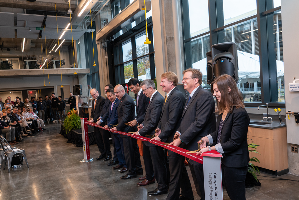 Ribbon cutting ceremony with nine people