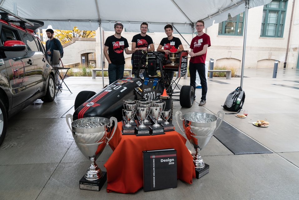 Student racing team posing with their car as well as numerous trophies they have received