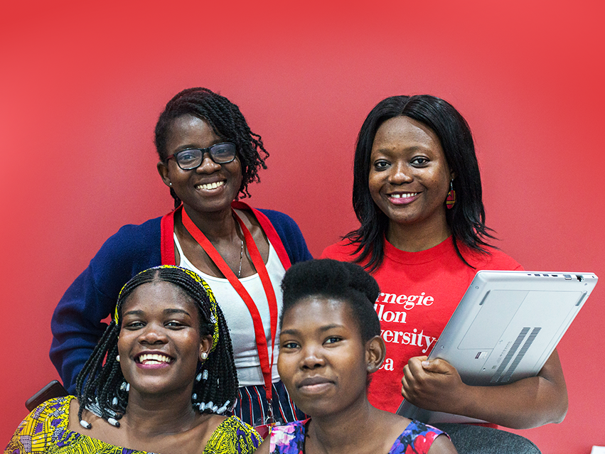 Photo of four female CMU-Africa students, one holding a laptop