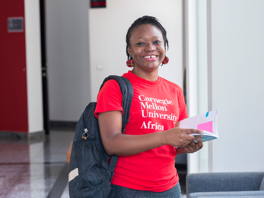 A CMU-Africa student in the halls holding a book