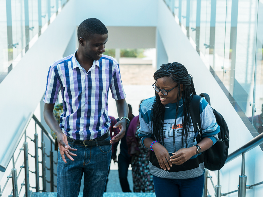 Two CMU Africa students chatting while walking up steps in the building