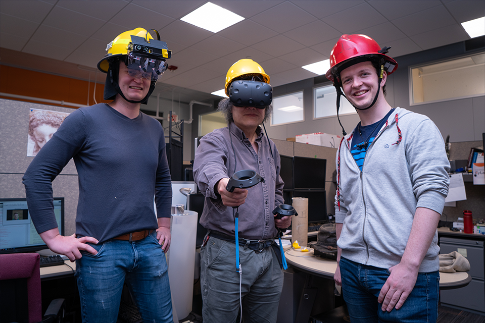 Three researchers in a lab wearing prototype helmets