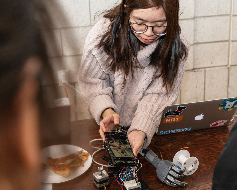 A student holding a phone next to a robotic arm