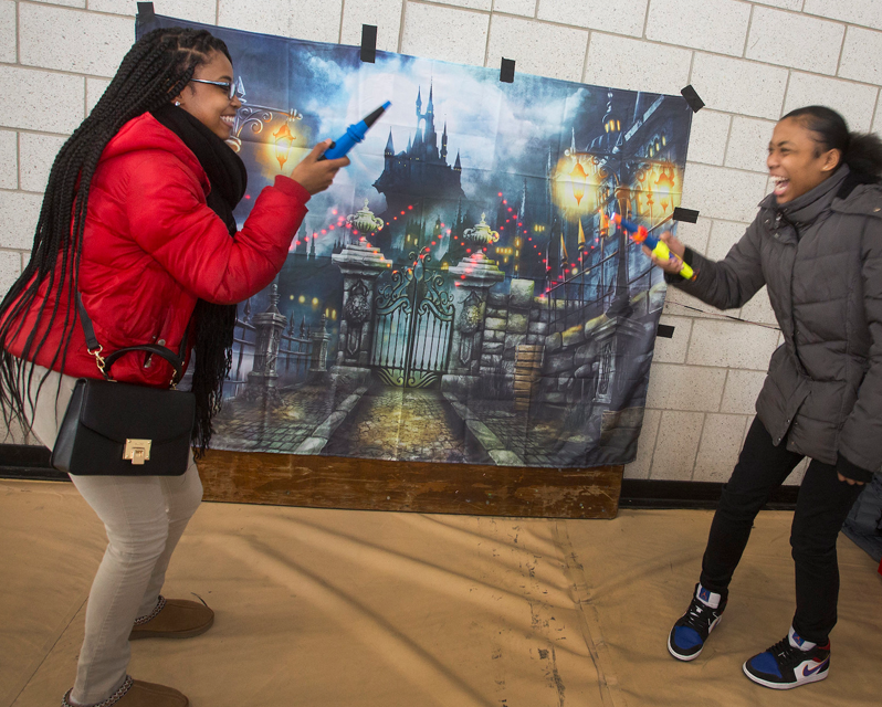 "Students with ""wands"" in front of a picture of a castle"