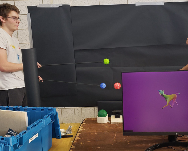 Student moving small spheres in front of a black background