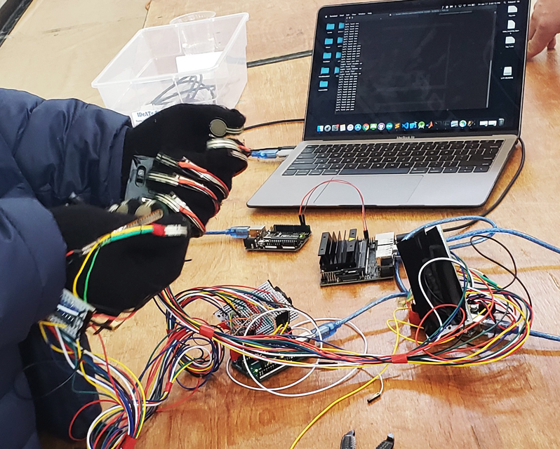 Gloves with multi-colored wires connected to a laptop