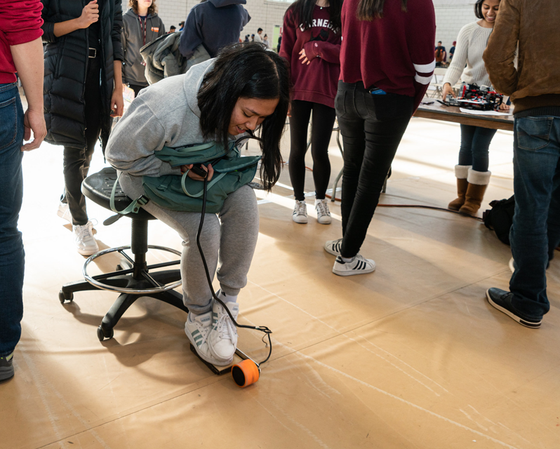 A student sitting on a rolling chair and pressing on a level on the floor with her shoes