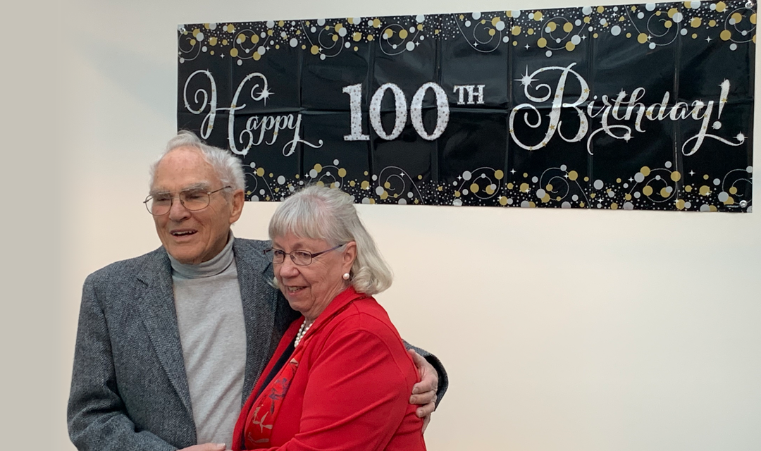 "Meyer and a woman in from of a ""Happy 100th birthday!"" banner"